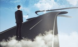 Research concept. Back view of young businessman standing on abstract futuristic blue sky road with clouds and airplanes. Research concept. 3D Rendering Royalty Free Stock Image