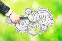 Research concept. Businessman hand holding magnifier over cogwheel sketch on abstract green background. Research concept stock images