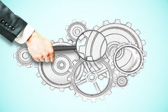 Research concept. Businessman hand holding magnifier over cogwheel sketch on light blue background. Research concept Stock Image
