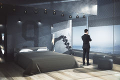 Research concept. Businessman looking out of window in male bedroom interior with panoramic view. Research concept. 3D Rendering Stock Photos