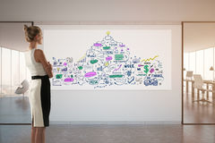 Research concept. Side view of woman looking at business sketch drawn on banner while standing in concrete office interior with city view. Research concept. 3D Stock Images