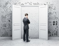 Research concept. Thoughtful businessman in brick room with closed door and business sketch. Research concept. 3D Rendering Stock Image
