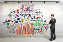 Research concept. Thoughtful young man in suit looking at white brick wall with creative business sketch. Research concept Royalty Free Stock Images