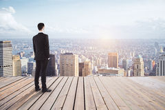 Research concept. Young businessman on pier looking at city with sunlight and copy space. Research concept Royalty Free Stock Photo