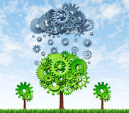 Research and development. Growing Profits with industrial investing in new rechnologies represented by a green tree and a grey rain cloud made of gears and cogs Royalty Free Stock Photos