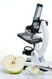 Research on healthy eating. Microscope and apple over white paper background suited for any medical or healthy lifestyle concepts royalty free stock photography