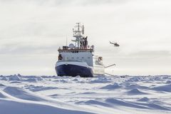 Research icebreaker and helicopter. Research icebreaker and a helicopter while setting up an ice camp Stock Image