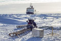 Research icebreaker and snowmobile. With sledges while setting up an ice camp Stock Photo