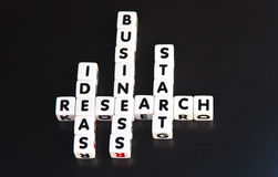 Research ideas start business. Research ideas lead to business start-ups concept using small white cubes inscribed with uppercase letters and presented crossword Royalty Free Stock Photography