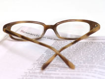 Research on the Internet. Glasses sitting on a page focusing on the word Research Stock Image