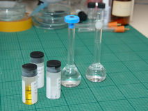 Research lab desk with samples in test-tubes. Scientific research laboratory, desk with liquid and crystal samples in test-tubes and flasks Stock Photo