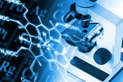 Research microscope with molecule structural formula and periodi Stock Images