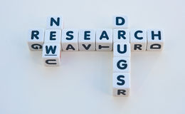 Research for new drugs. Text ' research ', 'new ' and ' drugs ' inscribed in black uppercase letters on white cubes, bright background Royalty Free Stock Image