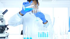 Research Scientist Pouring Chemical in Beaker for Reaction in Laboratory. 4k , high quality Stock Images