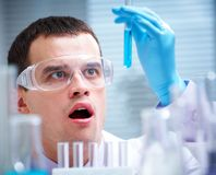 Research studies. Man scientist holding a test tube with liquid Stock Image