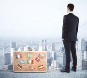 Research and travel concept. Businessman with suitcase on city background. Research and travel concept Royalty Free Stock Images