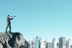 Research and vision concept. E view of young businessman on cliff looking into the distance on blue sky background with city skyline and copy space. Research and stock photo