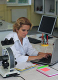 Researcher. Female researcher working on a laptop at her workplace in a laboratory Stock Photos