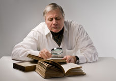 Researcher. Senior researcher exhamining a book with a magnifying glass Stock Image