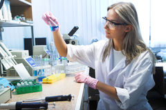 Researcher. Female researcher look at retort with blue liquid Royalty Free Stock Photo