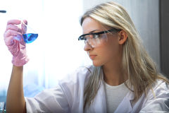 Researcher. Female researcher look at retort with blue liquid Royalty Free Stock Image