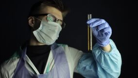 A young caucasian doctor with glasses on wearing a disposable mask. Looking at a bulb with solution. Dark background