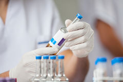 Researcher Analyzing Sample In Bottle. Midsection of male researcher analyzing sample in bottle at laboratory Stock Photos