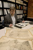 Researcher in archive, searching through maps and photographs. [Maps and photographs on table are public domain. Image on computer created for this photograph stock photos
