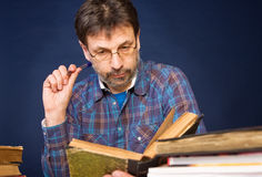 Researcher with the books. Mature man in glasses reading his book Royalty Free Stock Photos