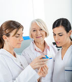 Researcher With Colleagues Reading Medicine Stock Images