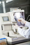 Researcher Examining Samples By Urine Analyzer. Cropped image of male researcher examining samples by urine analyzer in lab Royalty Free Stock Photos
