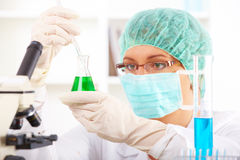 Researcher holding up a test tube and a retort royalty free stock images