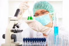 Researcher holding up a test tube and a retort Stock Images