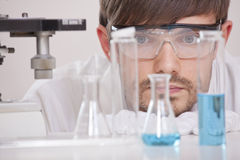 Researcher in Laboratory. Thinking male chemical researcher with many colourful flasks in a lab Stock Images