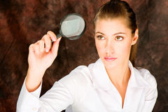 Researcher looking through magnifier glass. Pretty female researcher looking through magnifier glass Stock Image