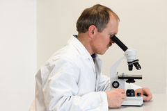 Researcher looking through microscope Royalty Free Stock Photo