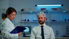Researcher neurologist asking man's symptoms taking notes on clipboard