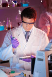 Researcher pipetting in laboratory. Stock Photos