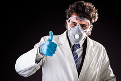 Researcher with protective gear thumb up. A joung and handsome doctor or researcher with a white lab coat and a protective mask royalty free stock images