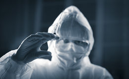 Researcher in protective suit preparing a syringe Royalty Free Stock Photo