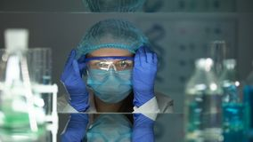 Researcher putting on protective eyeglasses before working with chemical agents stock video footage