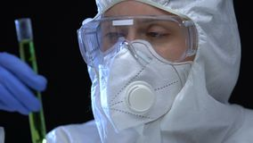 Researcher showing radioactive liquid sample in tube, mass destruction weapon