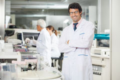 Researcher Standing Arms Crossed. Portrait of smiling male researcher standing arms crossed in laboratory near centrifuge Royalty Free Stock Photo