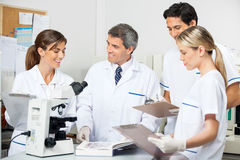 Researcher With Students Taking Notes In Lab Royalty Free Stock Photos