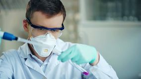 Researcher with tube and dropper in the modern lab.  stock video footage