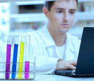 Researcher working on a laptop. Portrait of a young male researcher working on a laptop computer while carrying out research in a lab (the focus is on the test Stock Image