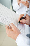 Researcher Writing On Clipboard. Cropped image of researcher writing on clipboard in laboratory Royalty Free Stock Photo