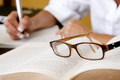 Researcher writing with glasses Royalty Free Stock Image