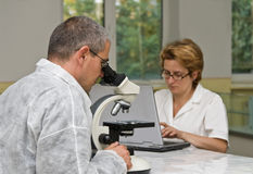 Researchers. Two researchers working together with a microscope Royalty Free Stock Photography