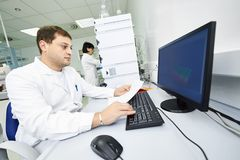 Researchers analyzing liquid chromatography data. Pharmaceutical scientific male researcher analyzing liquid chromatography data at pharmacy industry manufacture Stock Images